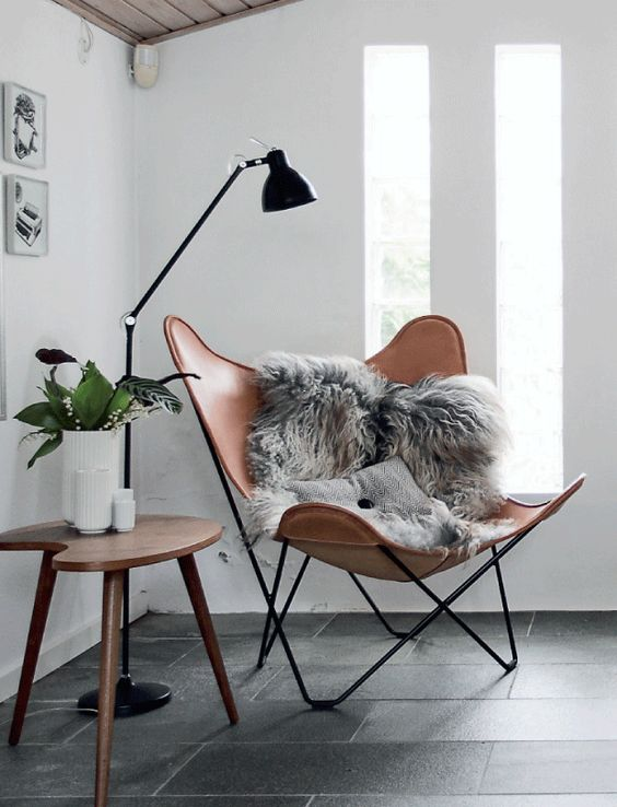 a very chic leather chair with faux fur and a Scandinavian floor lamp for a stylish reading nook