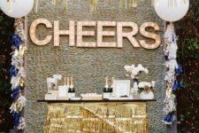 15 a drink station with gold fringe, gold fringe garlands and marquee lights
