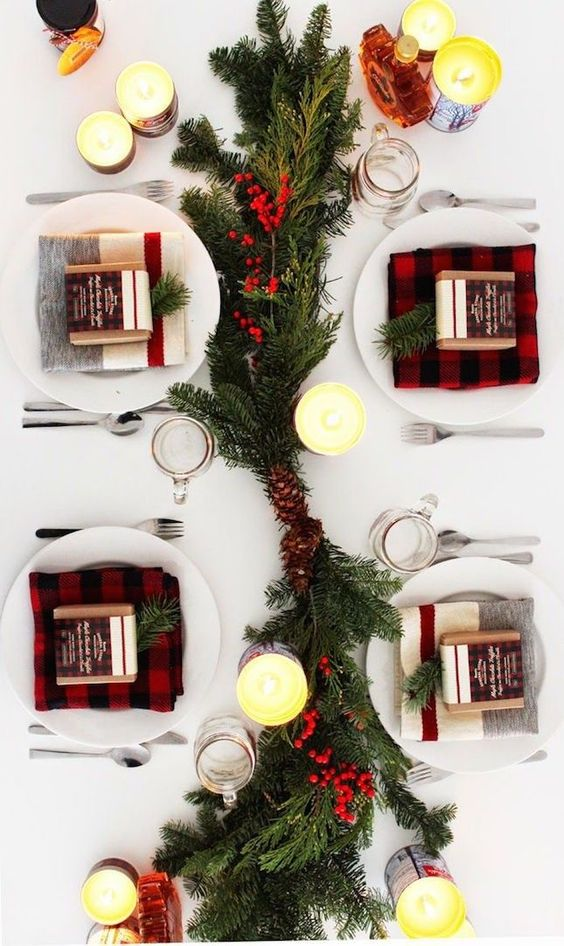 a modern take on a traditional tablescape with plaid, evergreens, pinecones and berries and lots of candles