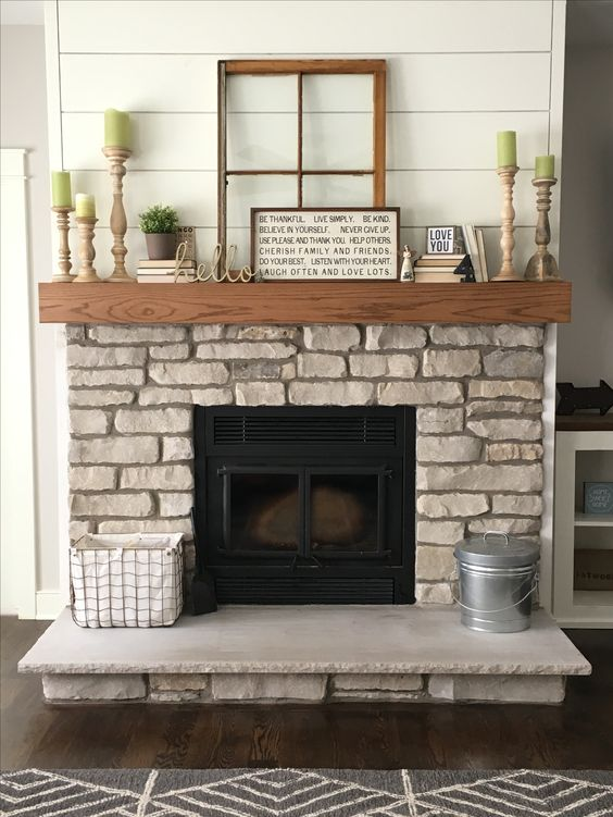 a natural stone fireplace with a wooden mantel looks very rustic, and you may add some rustic details