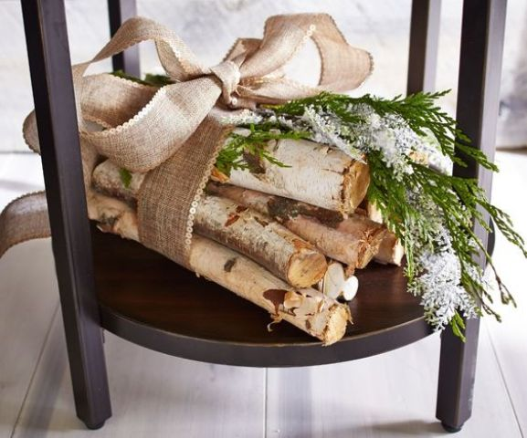 an arrangement of tree branches with greenery and a huge burlap bow