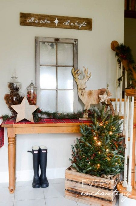 an old window, jars with pinecones and candies, wooden decor and some evergreen trees in a crate for a rustic look