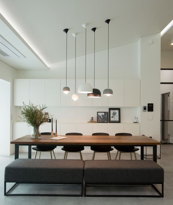 minimalist white cabinets and a stained dining table plus upholstered benches for a chic space