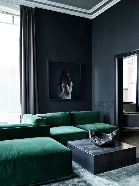 two mistakes in one room, black walls and a too large sofa steal the whole space