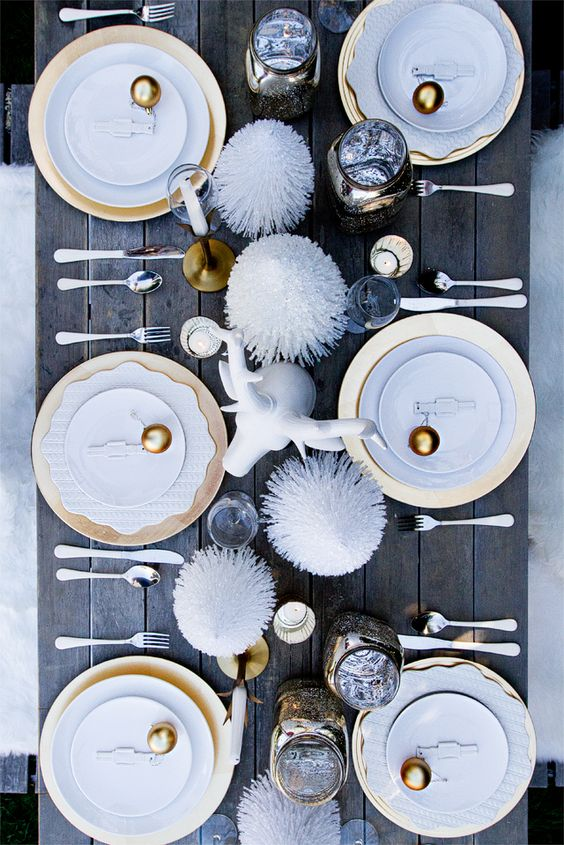 a fun holiday table setting with gold ornaments, pipe cleaner treesm a faux animal head and gold chargers