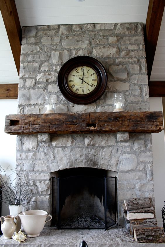 a grey stone fireplace, a reclaimed beam mantel and metal fireplace covers