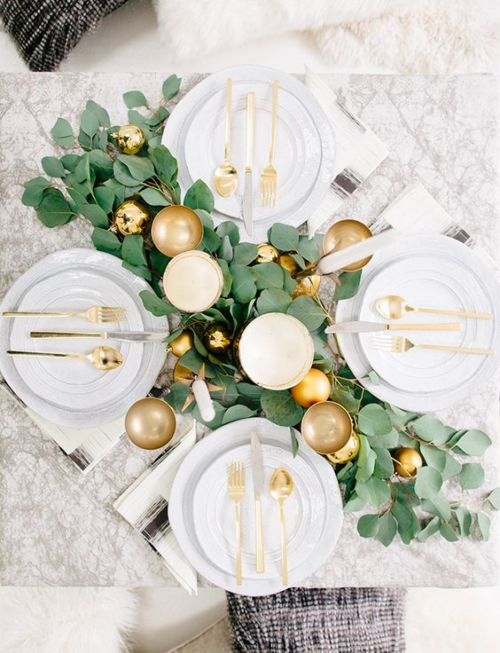 a lush foliage table runner with fold ornaments and gold goblets for a simple and elegant look