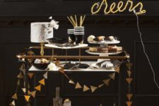 16 a simple black bar ccart decorated with a gold foil triangle garland and a neon sign