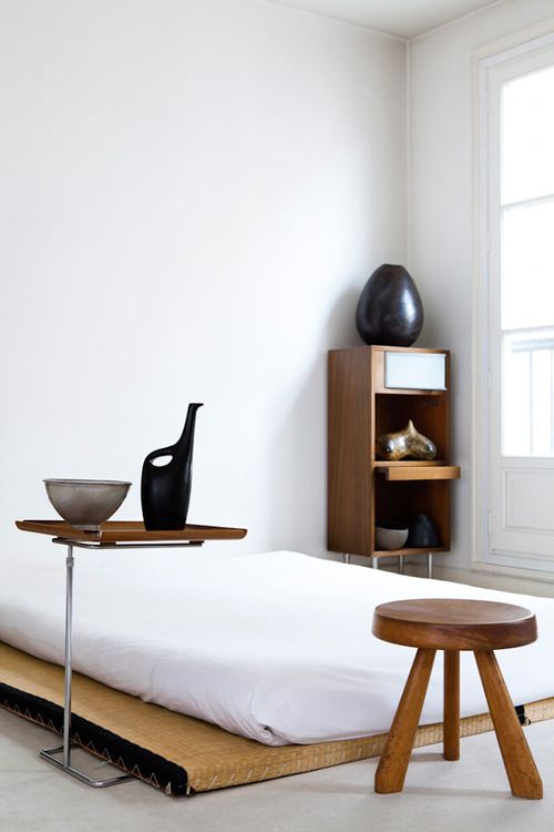 a traditional Japanese bed and some creative wooden furniture that contrasts white walls