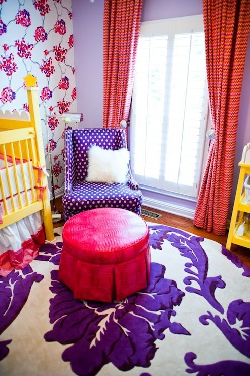 a violet polka dot chair in the nursery and a violet and white floral print rug
