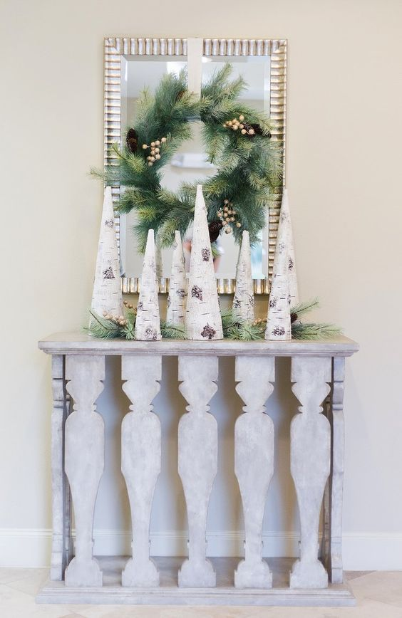 birch bark wrapped cone trees, evergreens and an evergreen wreath on a mirror
