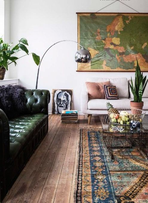 a dark green tufted leather sofa for a boho room with lots of greenery in pots