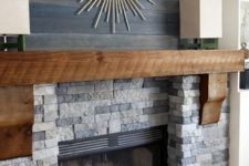 17 a faux stone clad fireplace with a wooden mantel and dark stained reclaimed wood over the mantel