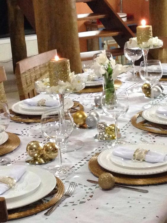 a holiday tablescape with gold and silver ornaments, wicker chargers, glitter candles and white blooms