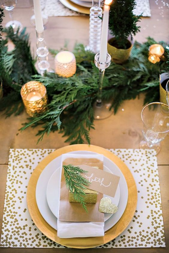 a modern glam tablescape with a gold sequin placemat, evergreens, gold mercury glass candle holders and glitter touches