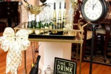 17 a stylish drink bar cart in black and gold with black and gold balloons and a large bow