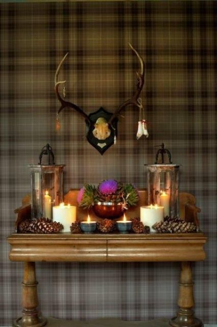 large pinecone, candles an candle lanterns with antlers over the console for a woodland-inspired space
