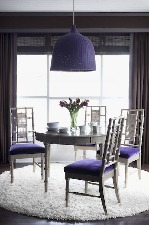 violet upholstered chairs and a matching wicker pendant lamp over the table