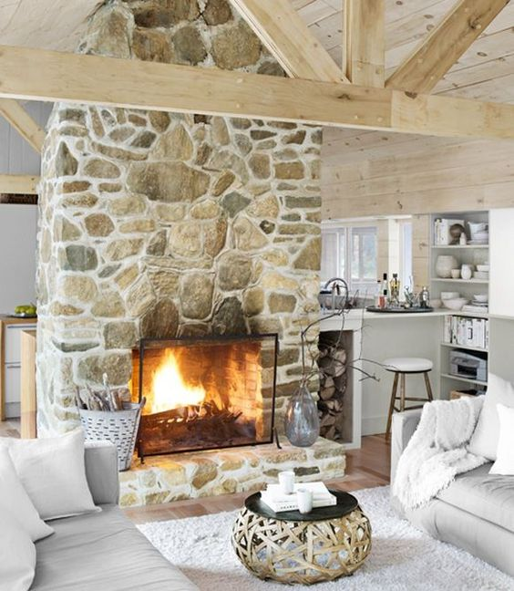 a gorgeous stone fireplace in light shades with a metal cover looks very genuine