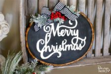 18 a raw edge wood slice chalkboard Christmas sign with pale millar, a striped ribbon and some berris