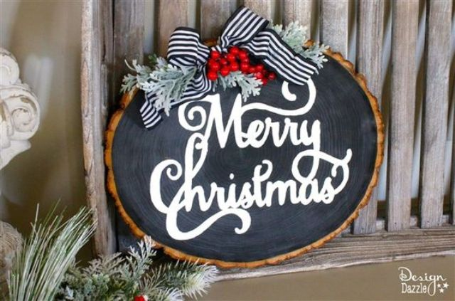 a raw edge wood slice chalkboard Christmas sign with pale millar, a striped ribbon and some berris