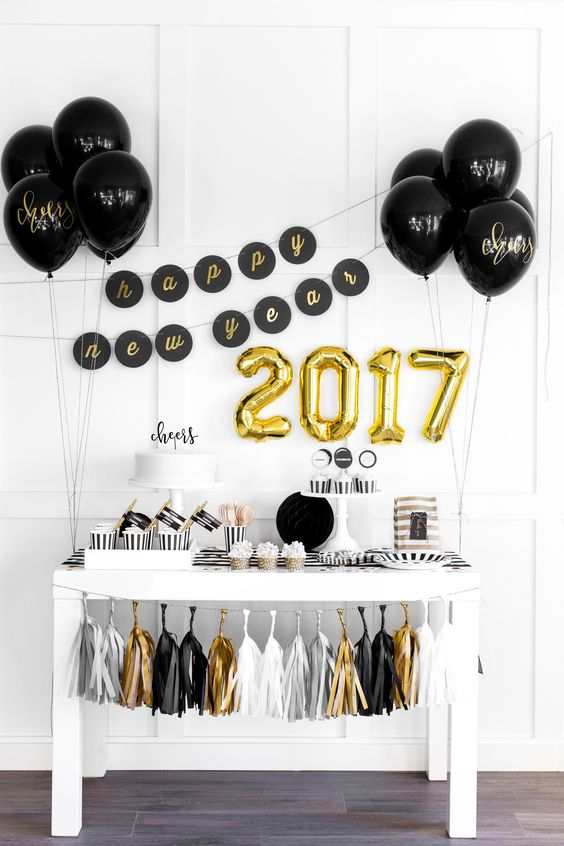 gold number balloons and black balloons with gold calligraphy for decorating a dessert table