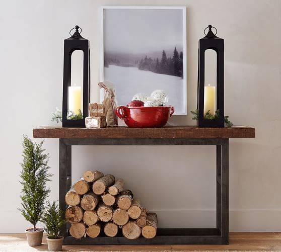 tall candle lanterns, a red bowl with ornaments, firewood and evergreen trees under the console