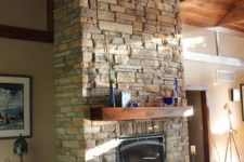 19 a rustic stone clad fireplace with a wooden mantel surrounded with candles