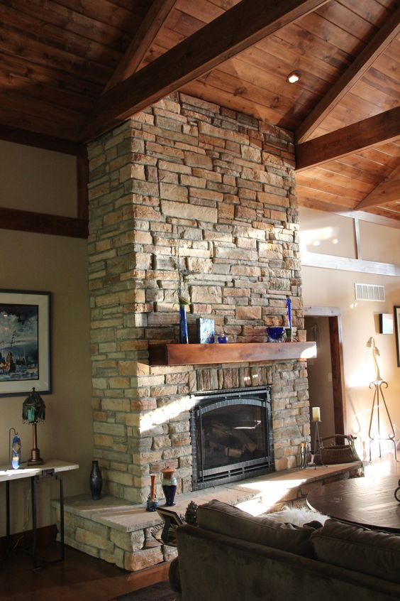 a rustic stone clad fireplace with a wooden mantel surrounded with candles