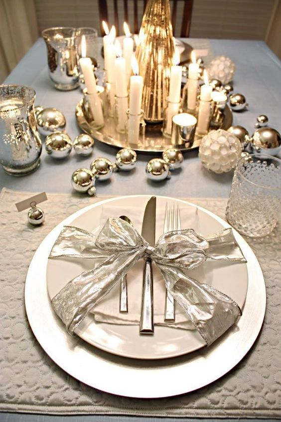 a shiny table setting with silver ornaments, mercury glass candle holders and candles