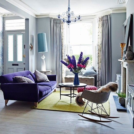 a violet upholstered sofa and a matching chandelier will add color to the space