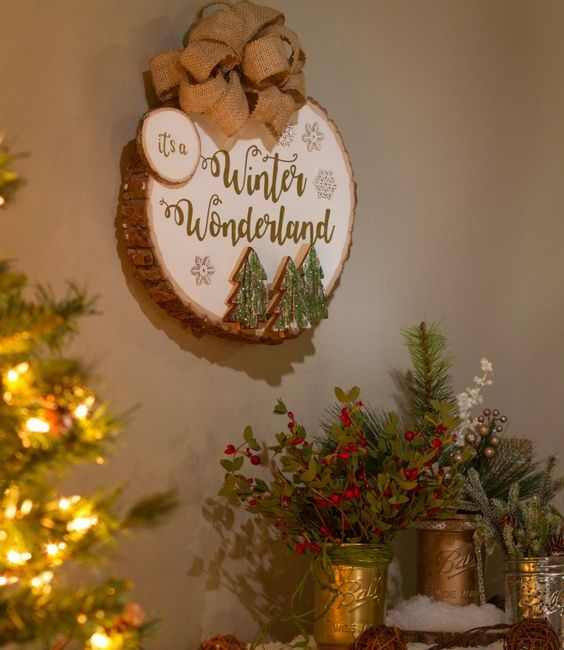 a winter sign with a large burlap bow, Christmas trees attached, snowflakes and calligraphy