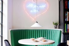 20 a chic retro diner breakfast nook with a neon sign, an emerald sofa and printed chairs