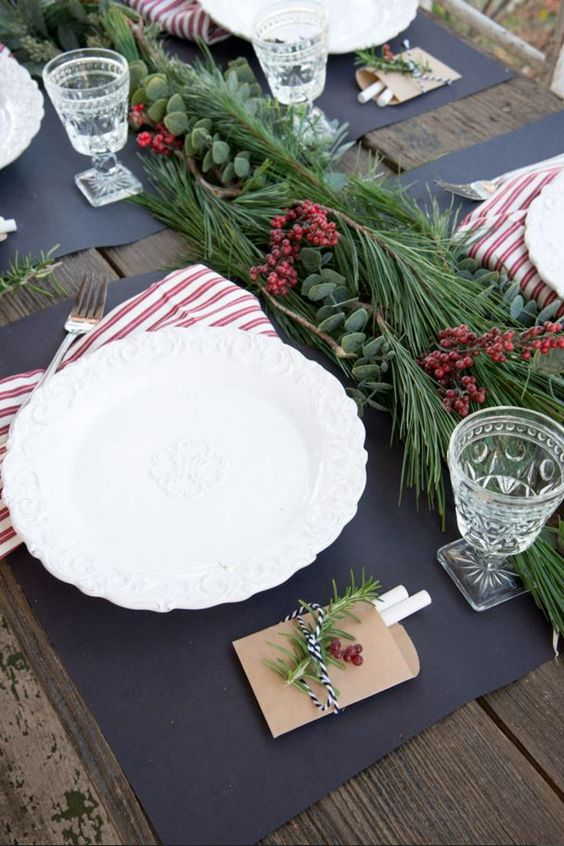 a modern tablescape with an evergreen and berry garland and striped napkins