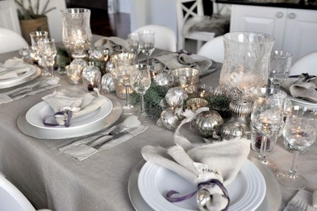 a silver grey tablescape with ornaments, glasses, jingle bells and silver chargers looks frosty and romantic