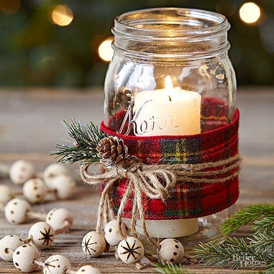 a candle holder made of a mason jar, with twine, a pinecone and evergreens