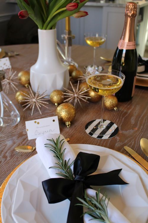 a sparkly tablescape with glitter ornaments, tulips, evergreens and black and white touches