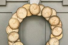 21 a wood slice Christmas wreath with a burlap bow and some dried herbs for a natural feel
