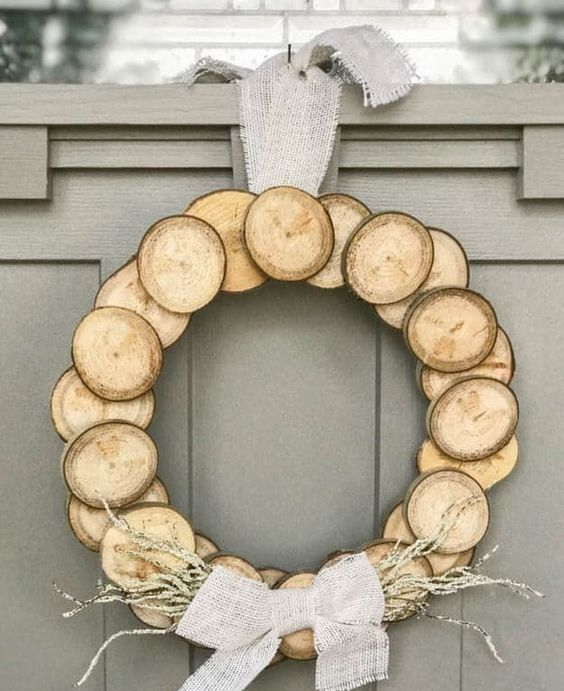 a wood slice Christmas wreath with a burlap bow and some dried herbs for a natural feel