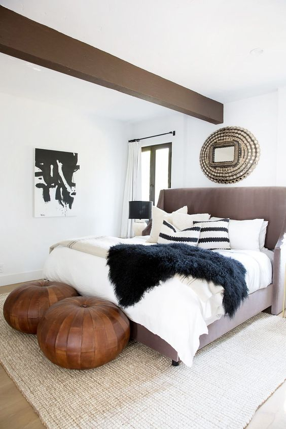 two brown leather round poufs add a Moroccan feel to the bedroom
