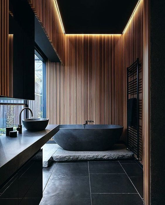 a Japandi bathroom with black and light-colored wood is highlighted with a natural stone slab and countertop