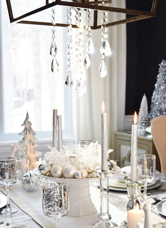 a white and silver table setting with pearly and silver ornaments, a crystal chandelier and patterned glasses