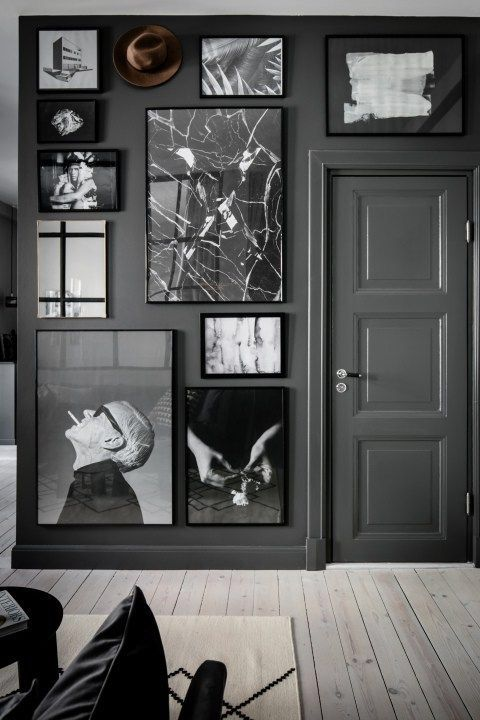 a grey space with a black and white gallery wall that takes the whole grey wall