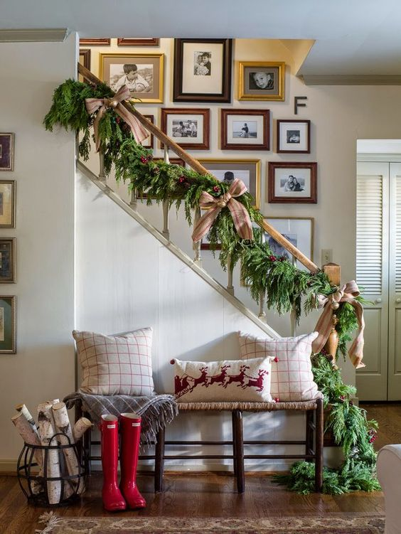 a lush evergreen garland with burlap bows and jingle bells for stairs decor