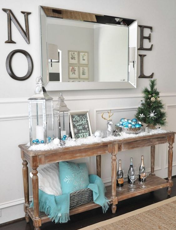 a vintage wooden console with faux snow, lanterns, a deer and turquoise touches