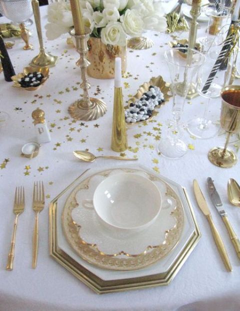 a white and gold tablescape with gold cutlery, goblets, candle holders and white blooms