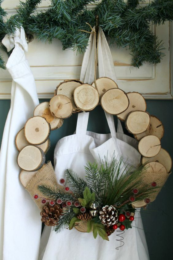 a wood slice Christmas wreath with faux evergreens, bells, berries and snowy pinecones for a rustic feel