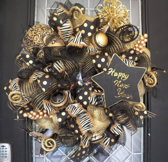 a chic sparkly black and gold wreath with ribbons, ornaments, a chanlkboard star and vignettes