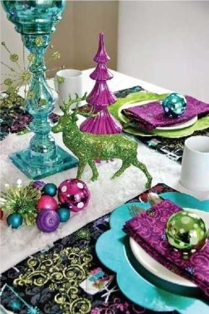 a colorful tablescape with ornaments, napkins and chargers of different colors and a glitter deer
