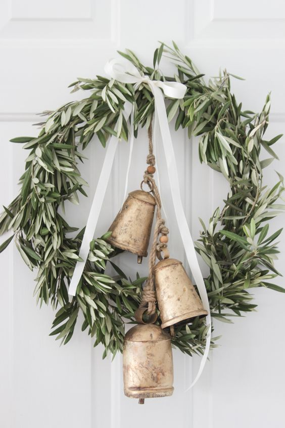a greenery wreath with a ribbon bow and large vintage bells will make your space farmhouse like at once